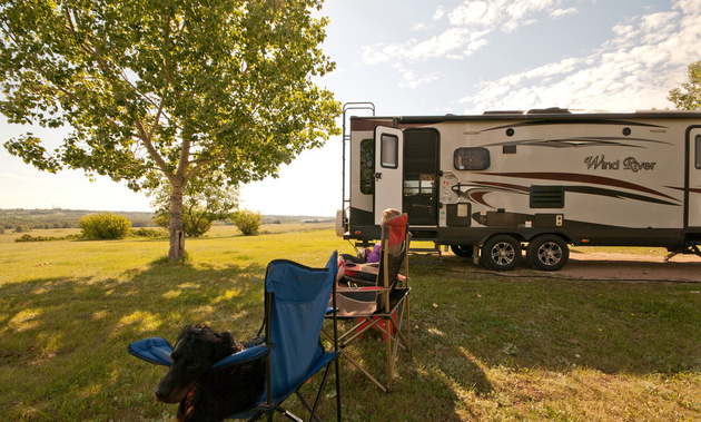 A person is sitting in a camp chair and eyeing the view in North Battleford, Saskatchewan, with an RV in the background.