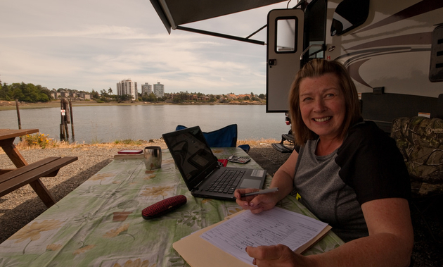 Working remotely takes a bit of planning. Here, a woman sits at a picnic table with a laptop and paperwork outside her RV.