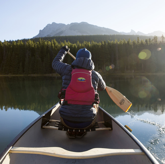 Person paddling a canoe by the mountains