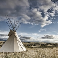 Photo of a teepee on the prairie.