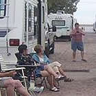 people sitting on lawn chairs in front of their RVs