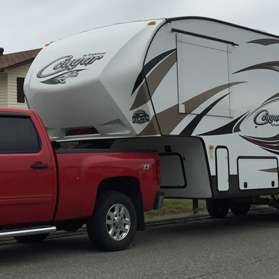 Picture of red truck towing fifth wheel trailer.