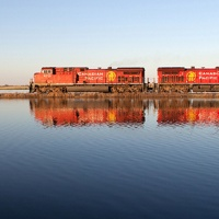 A CP train travelling across the rails with its reflection showing in a lake in the foreground.