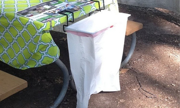A Trash-Ease bag attached to a picnic table.