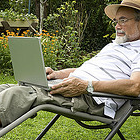 Man sitting in a lawn chair with a computer on his lap