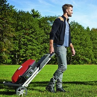 A young man walking through a park pulling a red TravelQ grill with him.