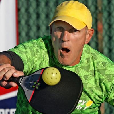 Pickleball player wearing yellow ball cap.