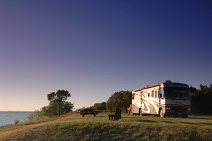 A man stands beside his RV and looks at the view of a lake.