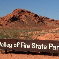 A photo of the Valley of Fire State Park sign with a red mountain in the background.