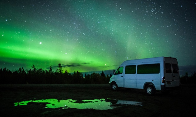 Ronn Murray's 8 passenger van with the aurora lights showing behind it.