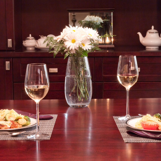 Two dinner place settings with wine glasses and white flowers are set on a wooden table.