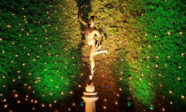 A sculpture in the Italian Garden at Butchart Gardens, with vibrant lighting behind the display.