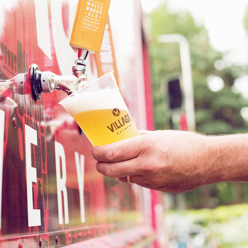 A man is filling a glass of beer from a beer tap at the Village Brewery.