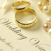 Photo of two wedding rings on top of paper with vows written on.