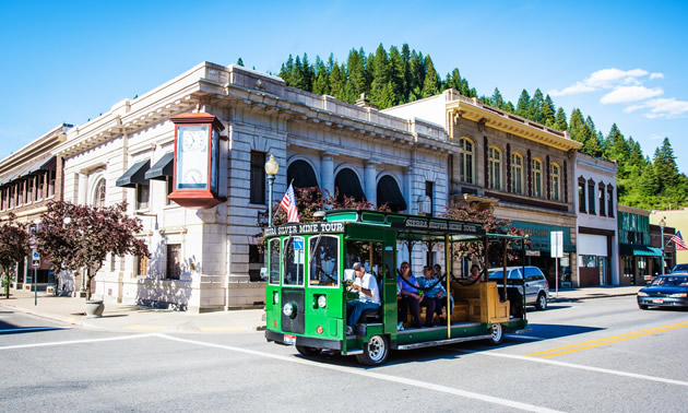 A green tour bus rides through downtown Wallace, the historic mining hub of Idaho.