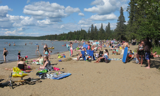 people gathered on a beach in Waskesiu Saskatchewan