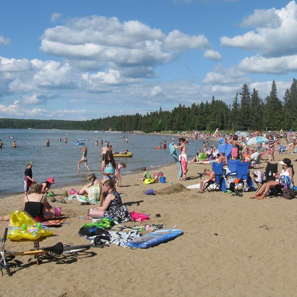 people gathered on a beach in Waskesiu Saskatchewan