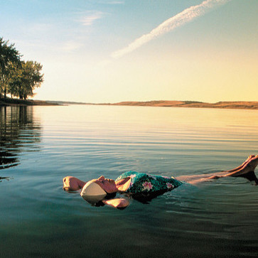 A woman floating in the minerals waters of Manitou Lake at sunset.
