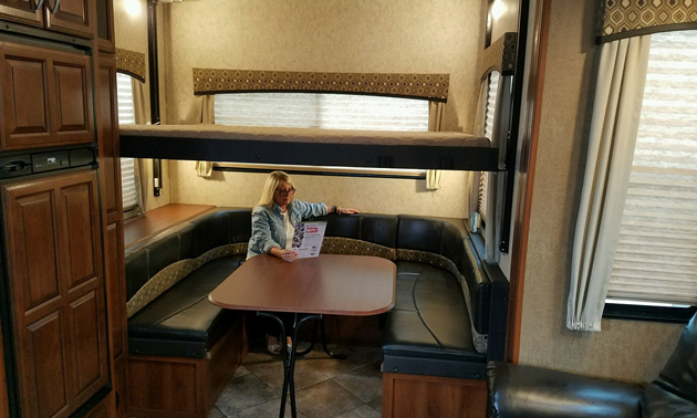 Picture of inside of RV, with woman sitting at table.