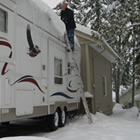 A man sweeps snow from the roof of an RV